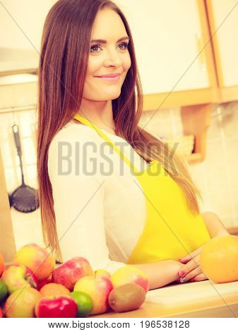 Health nature cuisine diet concept. Gorgeous cook preparing dish Younf girl wearing apron in kitchen making healthy food out of fruits.