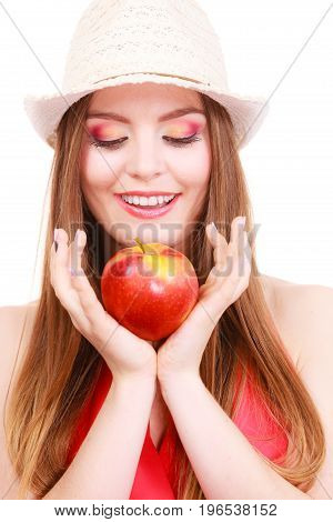Woman charming girl long hair colorful make up wearing summer hat holds big red apple fruit. Healthy eating vegetarian food dieting and people concept.