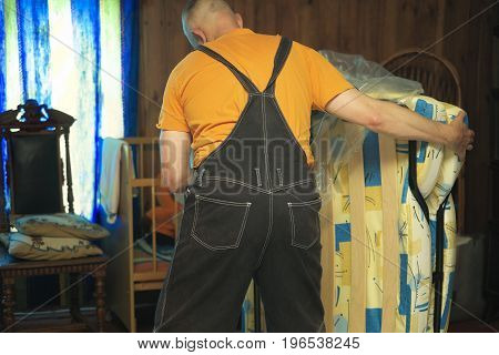 A worker moving a brand new furniture in cellophane wrap filtered indoor photo