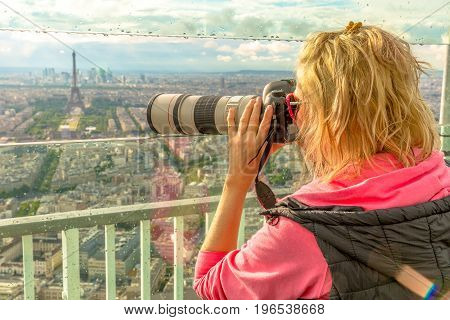 Traveler photographer takes photos of Tour Eiffel from observation deck of Tour Montparnasse. Woman photographer in French capital, Europe. Paris cityscape. Popular travel destination concept.