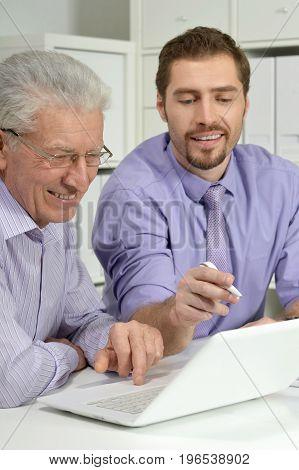 Portrait of two confident businessmen using laptop