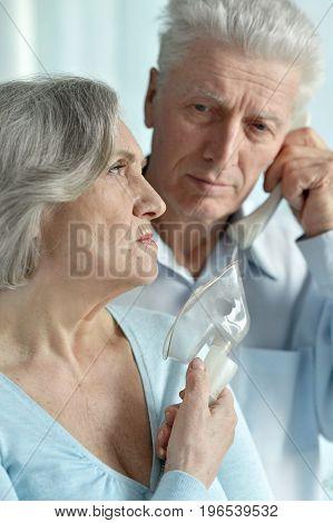 senior man taking care of ill senior woman and calling ambulance