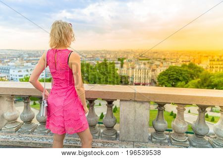 Parisian views from terrace of Sacre Coeur Cathedral, the highest city point of Paris, France, Europe. Elegant tourist woman admiring skyline of Paris from Sacred Heart viewpoint with dawn light.