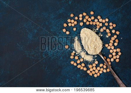 Old spoon with chickpea flour chickpeas on a blue background. view from above