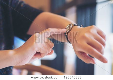 A business woman pointing at a black wristwatch on her working time while waiting for someone