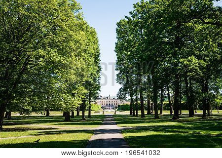 View over Drottningholm Palace from an alley in the park on a sunny summer day. Home residence of Swedish royal family. Famous landmark in Stockholm Sweden