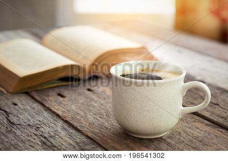 Coffee cup and open book on old wooden table with sunlight from window curtain bavkground
