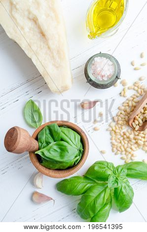 Fresh ingredients for pesto genovese sauce on white wooden table from above. Basil leaves in mortar Parmesan cheese pine nuts olive oil garlic and salt. Traditional Italian cuisine. Top view.