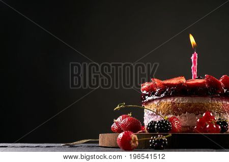 Wodden cake board with homemade raspberry-blackberry and strawberry birthday tart on dark stone table isolated on black background with copy space.