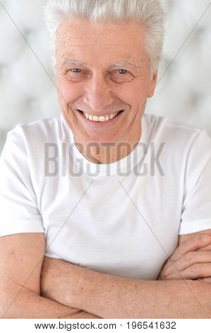 Close up portrait of smiling senior man in white t-shirt