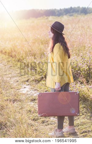 Beautiful young woman with brown vintage suitcase and black hat in the field road during summer sunset.