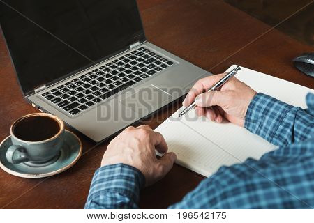Rear view shot of hands busy businessman writing by pen and using laptop at office desk.