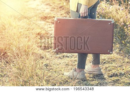 Beautiful young woman with brown vintage suitcase in the field road during summer sunset. Travel concept.