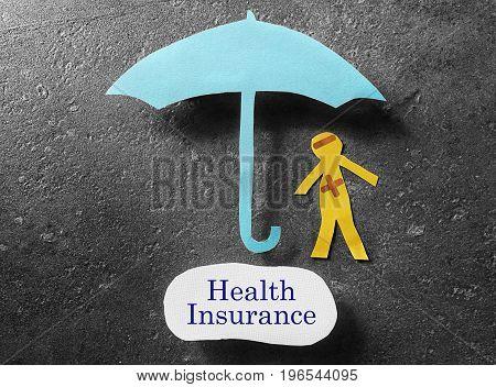 bandaged paper man under umbrella with Health Insurance label