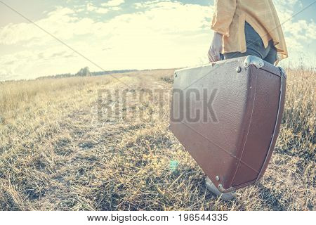 Beautiful young woman carries brown vintage suitcase in the field road during summer sunset. Toned image and travel concept.