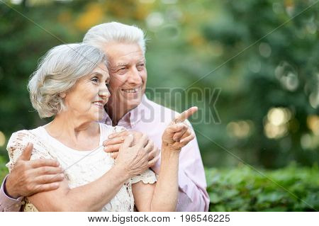 portrait of beautiful senior couple posing   in the park. woman pointing with finger