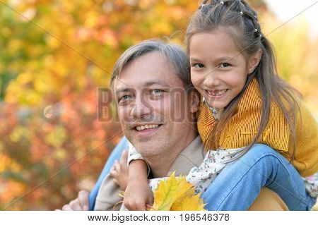 Portrait of father and daughter   outdoors. Man giving piggyback ride to girl