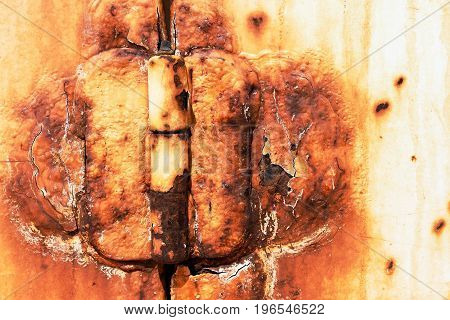 An abstract image of a very old and rusted metal door hinge.