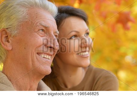 woman and senior man smiling  in autumn park