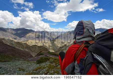 Tourist during expedition in the mountains Ladakh is admiring the beautiful Karakorum panorama.
