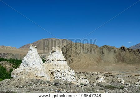 Old stupa in the Indusu valley in the Ladakh is admiring the beautiful Karakorum mountains.