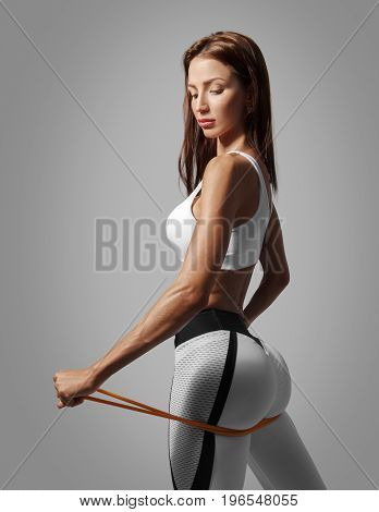 Photo of female buttocks in sports clothes. Sports lifestyle, beautiful, fit figure. Studio shoot on gray background with clipping path.