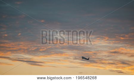 Passanger aircraft takes off into sky from international airport, sunset