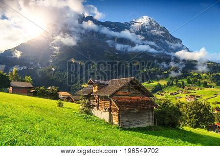 Fabulous alpine wooden houses green fields and famous touristic Grindelwald town with high North Face of Eiger mountains Bernese Oberland Switzerland Europe
