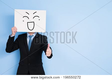businessman take happy billboard and thumb up on blue background