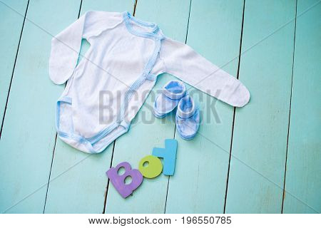 Children's clothing with an inscription boy on wooden boards