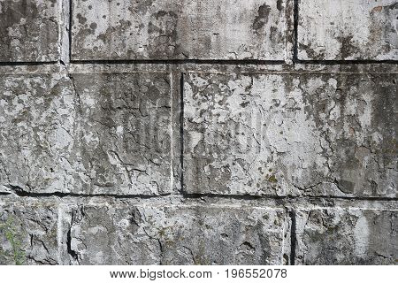 Old dirty wall with rectangular slabs and remains of a whitewash layer.