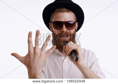People music show and entertainment concept. Handsome stylish bearded showman or presenter wearing trendy hat and sunglasses performing on stage holding microphone showing back of hand at camera