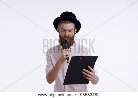 Studio shot of attractive young Caucasian male entertainer or host with thick beard wearing hat and shirt holding clipboard reading from notes in microphone. Bearded male singing a song in mic