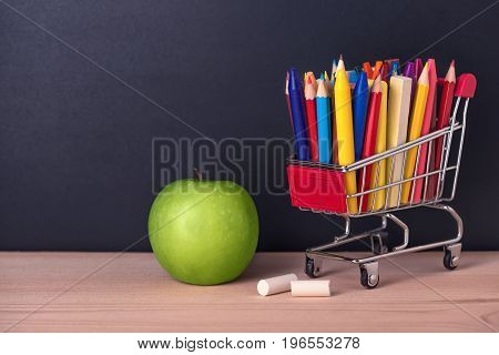 Education Concept With Green Apple, Chrome Shopping Cart, Pens, Crayons, Chalks On Black Chalkboard