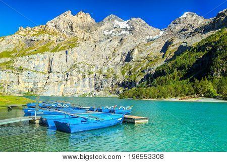 Amazing alpine lake and stunning mountains with blue boats Oeschinen lake Bernese Oberland Switzerland Europe