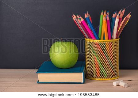 Education Concept With Green Apple, Book, Pencils, Chalks Over Black Chalkboard Background, Close Up