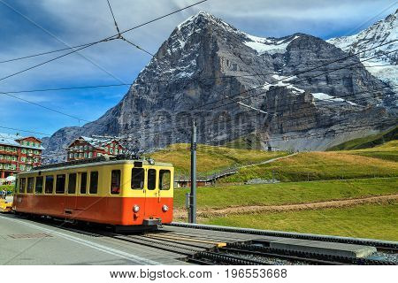 Famous retro electric red tourist train and Kleine Scheidegg train station with Eiger North Face in background Bernese Oberland Switzerland Europe