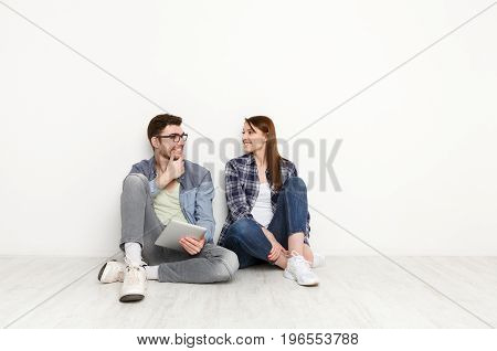 Couple discuss something, sitting on floor with tablet on white background at new apartment