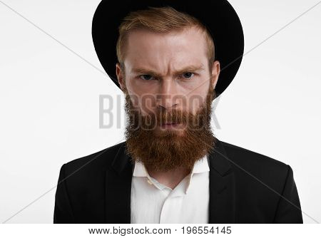 Headshot of grumpy young European hipster with fuzzy ginger beard frowning having unhappy or angry expression on his face feeling displeased and dissatisfied with something wearing hat and suit