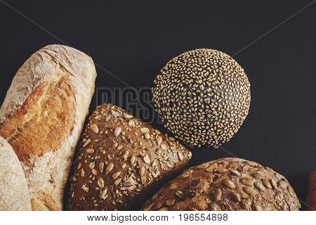 Bakery background, bread assortment on black with copy space. Rye buns and french baguettes top view, isolated