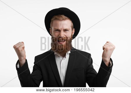 Successful lucky businessman in stylish headwear screaming Yes and raising clenched fists up in the air cheering enjoying his triumph victory success or good deal. Celebration and winning concept