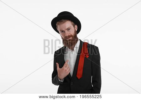 People style and fashion concept. Waist up shot of fashionable confident bearded young European man wearing trendy hat jacket and red tie on his shoulder looking at camera with serious expression