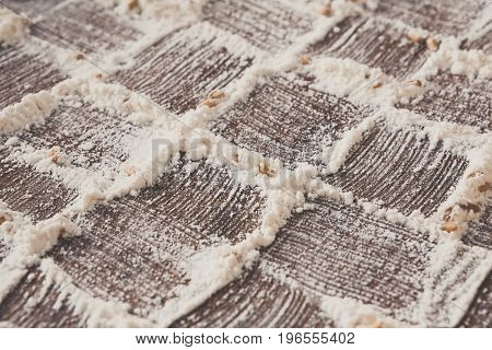 Baking concept, flour on rustic wood background, checkered pattern. Cooking dough or pastry.
