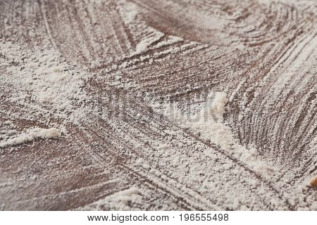Baking concept on wood background, sprinkled wheat flour with copy space. Cooking dough or pastry.