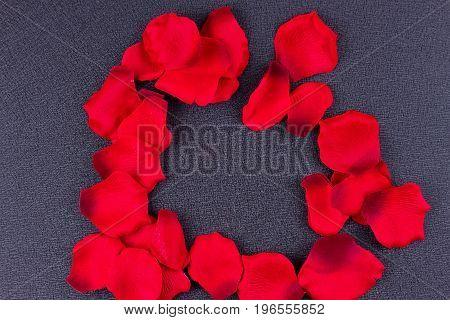 Artificial petals red roses black background frame