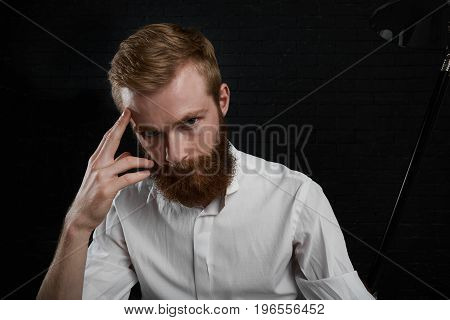 Job occupation profession and hobby. Headshot of attractive redhead young Caucasian professional photographer with thick beard dressed in white shirt looking at camera sitting in dark studio
