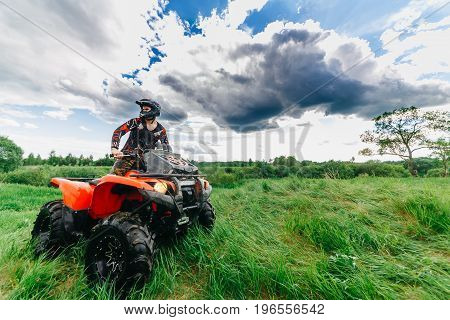 VITEBSK, BELARUS - JUNE 11, 2017: Photo of man on the ATV Quad Bike running in field.