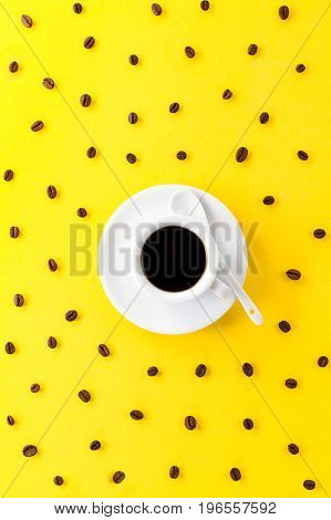 Coffee espresso in small white ceramic cup with many coffee beans on yellow vibrant background. Minimalism Food Morning Energy Concept.