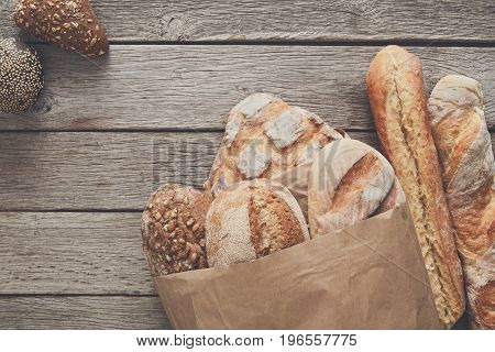 Bakery, bread in paper bag on rustic wood background, grocery concept.