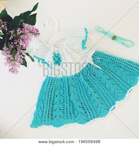 Knitted turquoise baby dress. Photo in square format